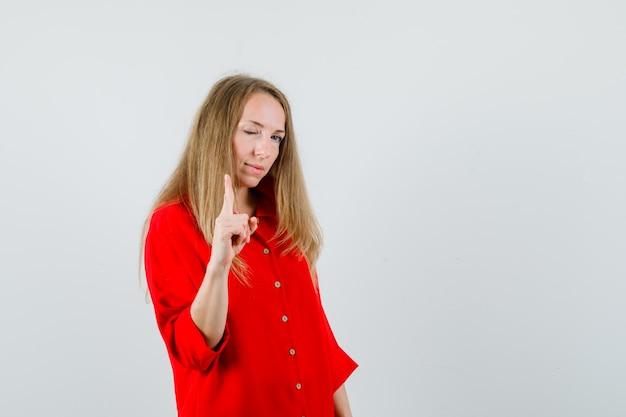 Senhora apontando um olho piscando em camisa vermelha e parecendo confiante.