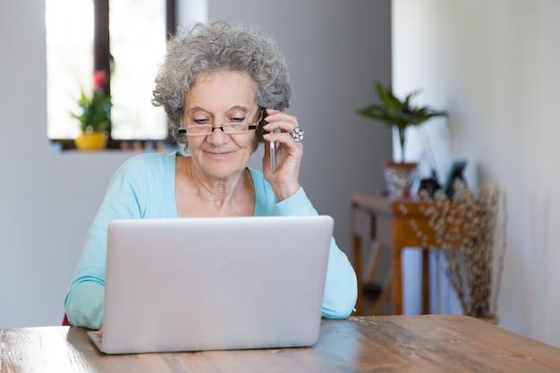 Senhora aposentada positiva que trabalha em casa