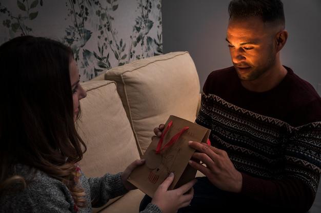 Senhora apresentando pacote de presente para o cara no sofá