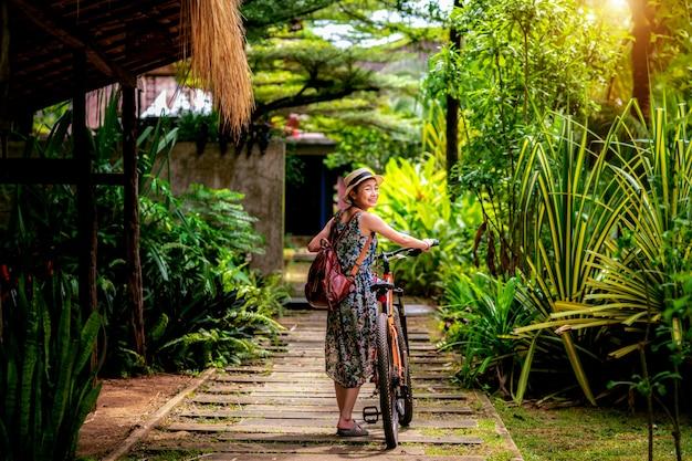 Senhora asiática alugar uma bicicleta no resort tropical em koh mak