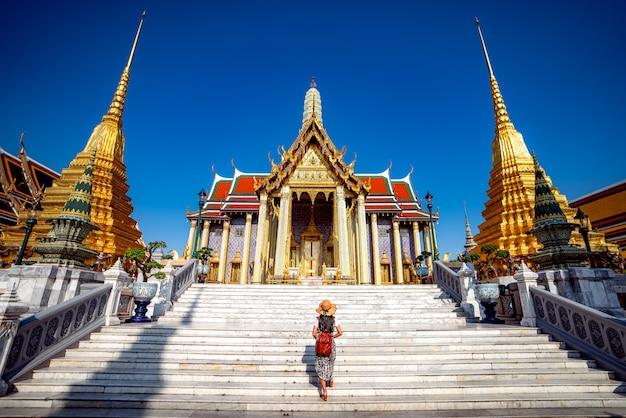 Senhora asiática andando e viajando em wat phra kaew