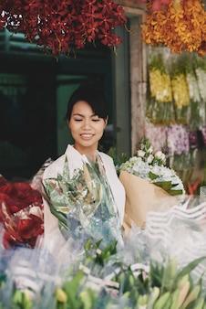 Senhora asiática bonita que escolhe flores na loja de florista