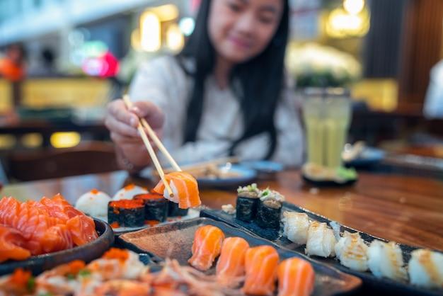Senhora asiática comer um sashimi de peixe salmão e sushi no restaurante japonês