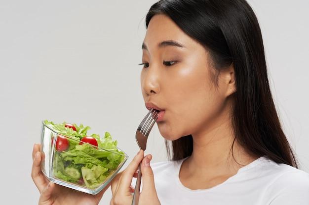 Senhora asiática, comer uma salada