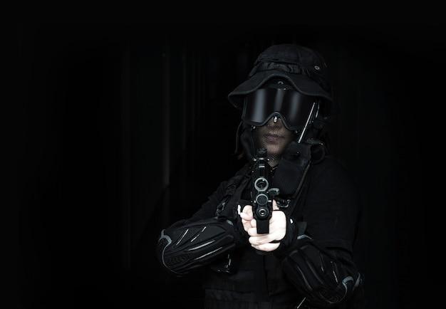 Senhora asiática em preto soldado bb arma esporte jogo traje e arma