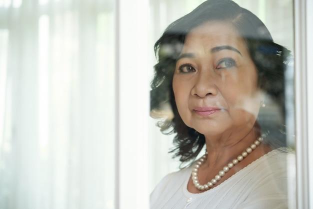 Senhora asiática idosa, olhando para fora através do vidro da janela