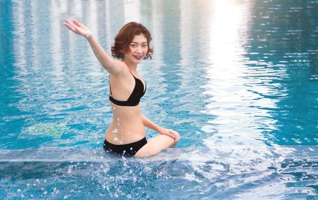 Senhora asiática na suite de natação jogando água postando na piscina de água.