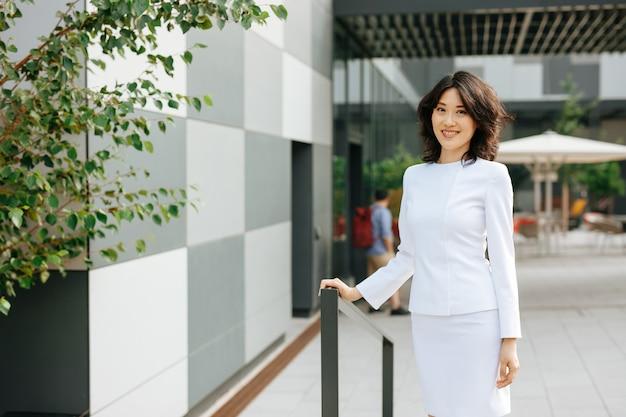 Senhora asiática no terno de negócio em pé perto do centro de escritório