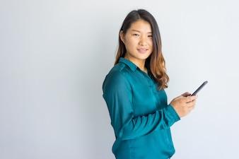 Senhora asiática segura positiva do negócio que usa o dispositivo e olhando a câmera.