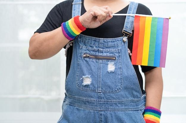 Senhora asiática segurando a bandeira com a cor do arco-íris, símbolo do mês do orgulho lgbt, comemora anualmente em junho