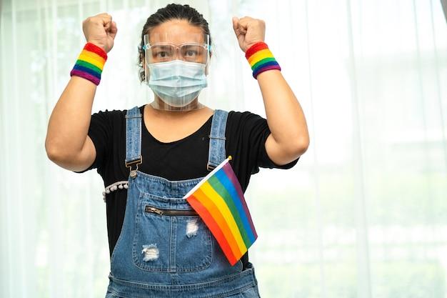 Senhora asiática segurando o símbolo da bandeira lgbt com a cor do arco-íris
