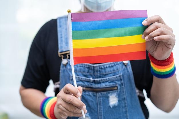 Senhora asiática segurando uma bandeira com a cor do arco-íris, símbolo do mês do orgulho lgbt