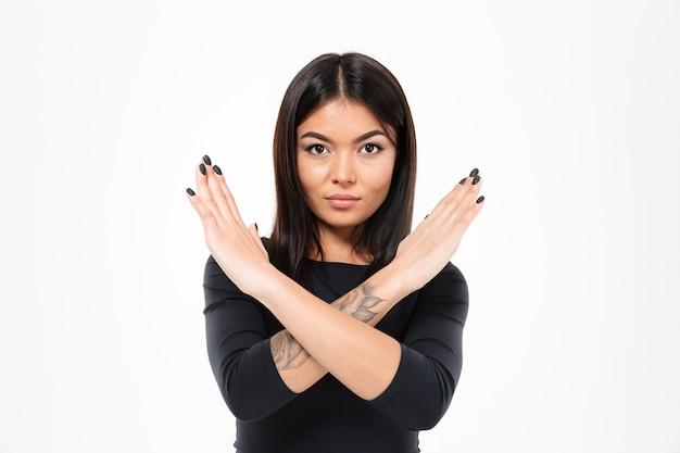 Senhora asiática séria concentrada nova que mostra o gesto da parada