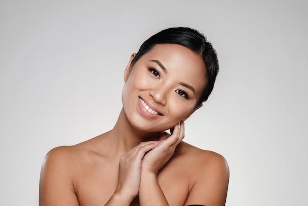 Senhora asiática sorridente, tocando sua pele clara