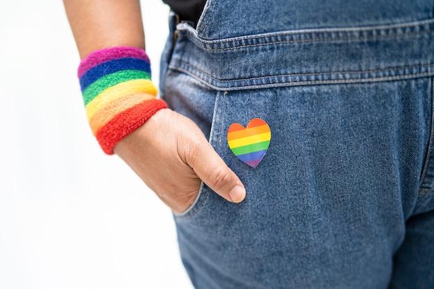 Senhora asiática usando pulseiras com a bandeira do arco-íris, símbolo do mês do orgulho lgbt, comemora anualmente em junho a socialização dos direitos humanos de gays, lésbicas, bissexuais, transgêneros.