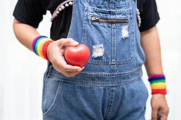 Senhora asiática usando pulseiras com bandeira do arco-íris e segurando um coração vermelho, símbolo do mês do orgulho lgbt, comemora anual em junho social dos direitos humanos de gays, lésbicas, bissexuais, transgêneros.