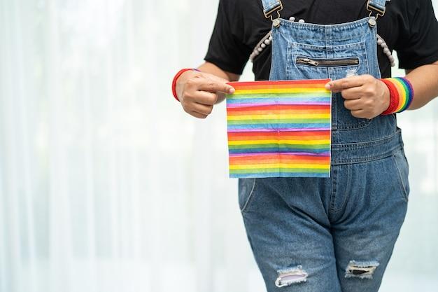 Senhora asiática vestindo jaqueta jeans azul ou camisa jeans e segurando uma bandeira com a cor do arco-íris