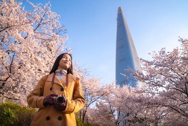Senhora asiática viajar e warking no parque flor de cerejeira