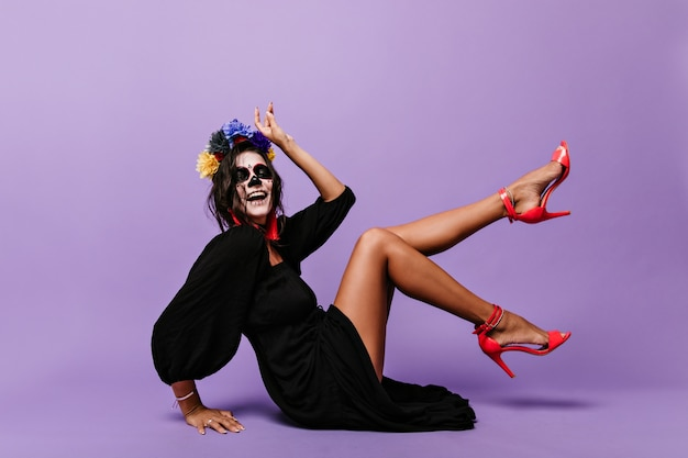 Senhora ativa com coroa de flores azuis mostra elegantes saltos altos cor de coral. retrato de uma menina brincalhona com máscara de caveira, sentada no chão.