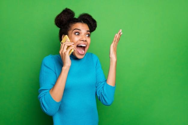 Senhora atônita e animada segurando telefone conversando