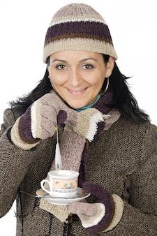 Senhora atraente abrigada para o inverno, bebendo uma xícara de chá