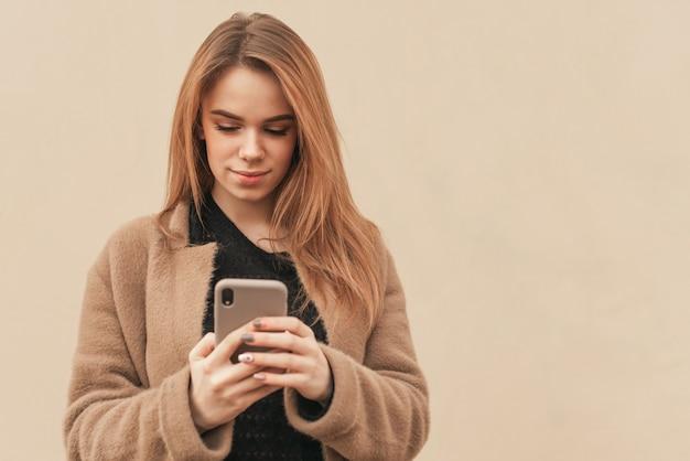 Senhora atraente com smartphone em mãos no fundo bege.