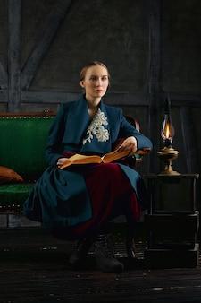 Senhora atraente lendo livro antigo perto da lâmpada de querosene vintage