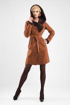 Senhora atraente no casaco de pele de carneiro marrom posando com capuz de pele na cabeça
