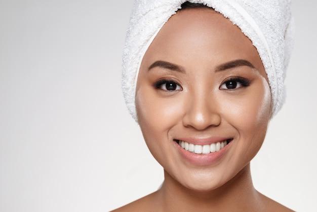 Senhora atraente sem maquiagem com toalha na cabeça, sorrindo para a câmera