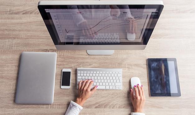Senhora atrativa do negócio que usa um computador moderno.