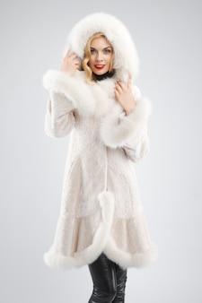 Senhora atrativa no casaco de pele branco com capuz na cabeça