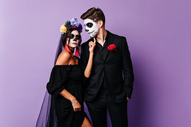 Senhora autoconfiante em um vestido de noiva preto com maquiagem de halloween toca o rosto do namorado enquanto ele olha para ela com ternura.