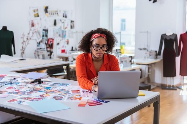 Senhora autônoma. mulher bonita e concentrada trabalhando com seu laptop enquanto está sentada em seu apartamento