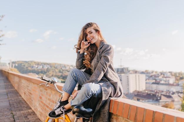 Senhora bem vestida e de bom humor, brincando, posando no fundo da cidade em um clima quente