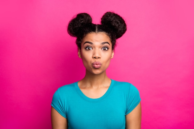 Senhora bonita de pele escura com penteado de dois coques mandando beijo no ar em fundo rosa