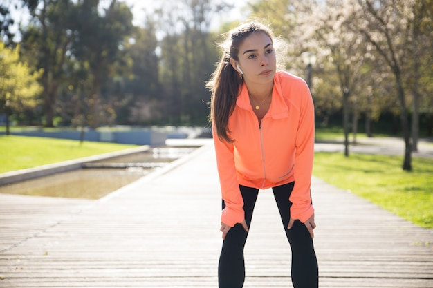 Senhora bonita desportiva, apoiando-se nos joelhos e relaxar no parque da cidade