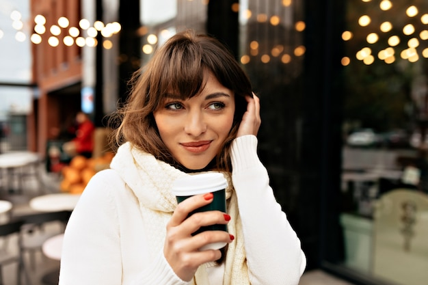 Senhora bonita e encantadora vestida de suéter branco e lenço bebendo café do lado de fora no fundo de luzes foto de alta qualidade