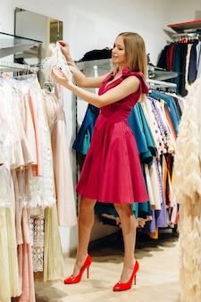Senhora bonita e sorridente escolhe um vestido bege com penas em uma loja de roupas