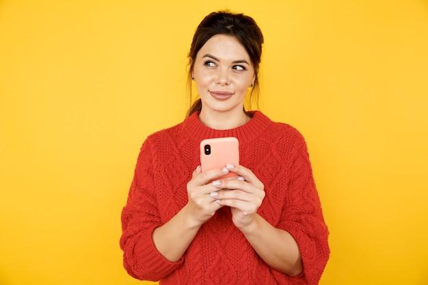 Senhora bonita em pose de pensamento com o telefone nas mãos isolado sobre o fundo amarelo.