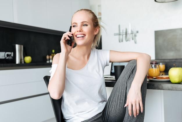 Senhora bonita feliz olhando de lado enquanto fala no telefone