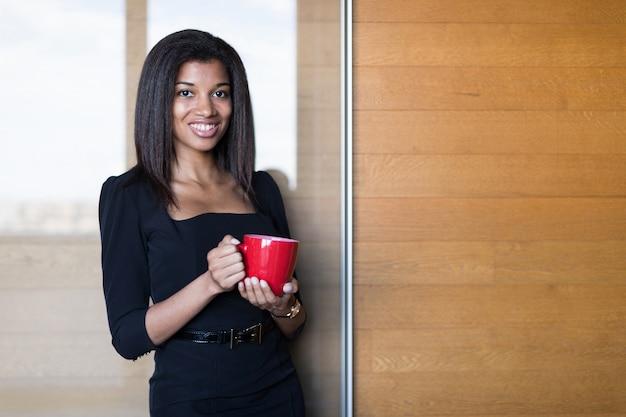 Senhora bonita, jovem de negócios na suite forte preta segurar copo vermelho