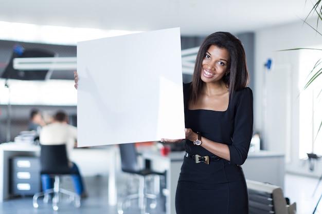 Senhora bonita, jovem de negócios na suite forte preto segurar cartaz em branco vazio
