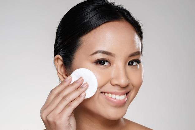 Senhora bonita, limpando o rosto com almofada de algodão