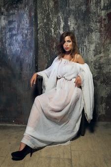 Senhora bonita mística no vestido branco gótico no calabouço subterrâneo
