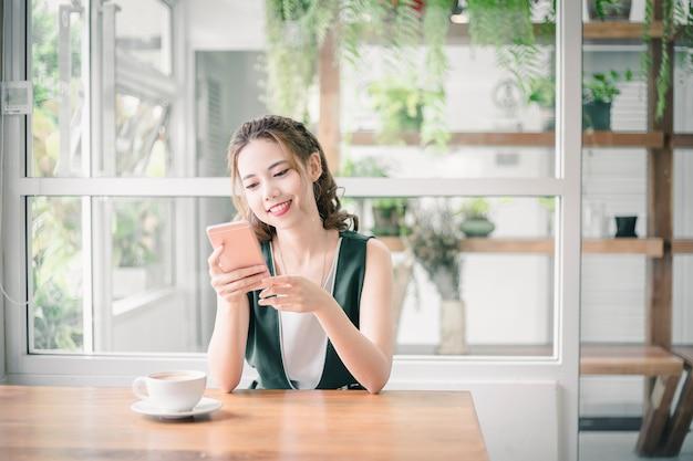Senhora bonita nova de asain que toca e que consulta em seu telefone esperto em casa.