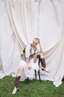 Senhora bonita que senta e que olha no vestido branco e cinzento no jardim e na parede branca durante o dia.