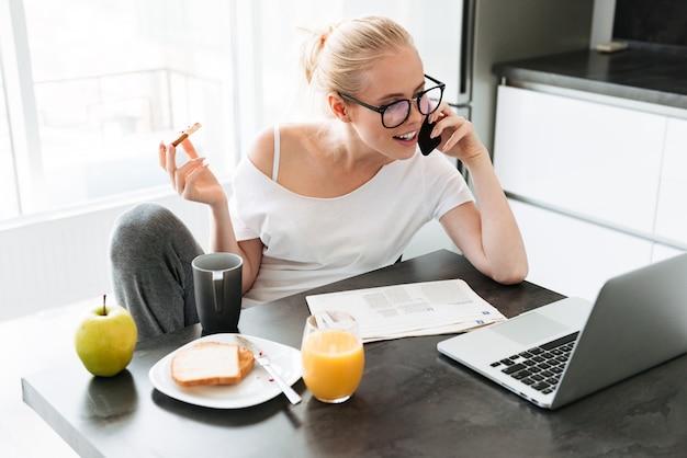 Senhora bonita trabalhando com laptop e falando no smartphone e tomando café da manhã