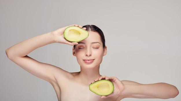 Senhora calma com abacate na parte superior e inferior nas duas mãos