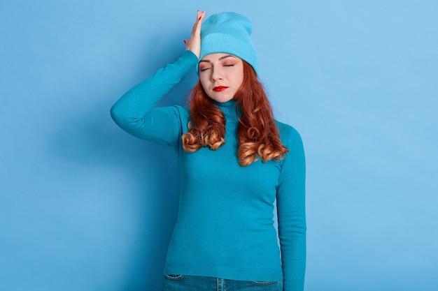 Senhora cansada com rolos vermelhos posando com os olhos fechados, sofrendo de uma terrível dor de cabeça, vestindo roupas casuais