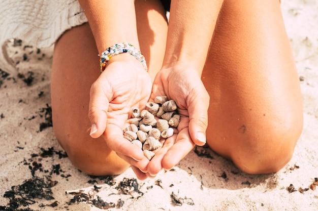 Senhora caucasiana pega um monte de conchas do mar para te oferecer como um presente ou para te mostrar. conceito de resort em uma ilha tropical para férias de verão em uma praia de areia branca com a natureza ao redor